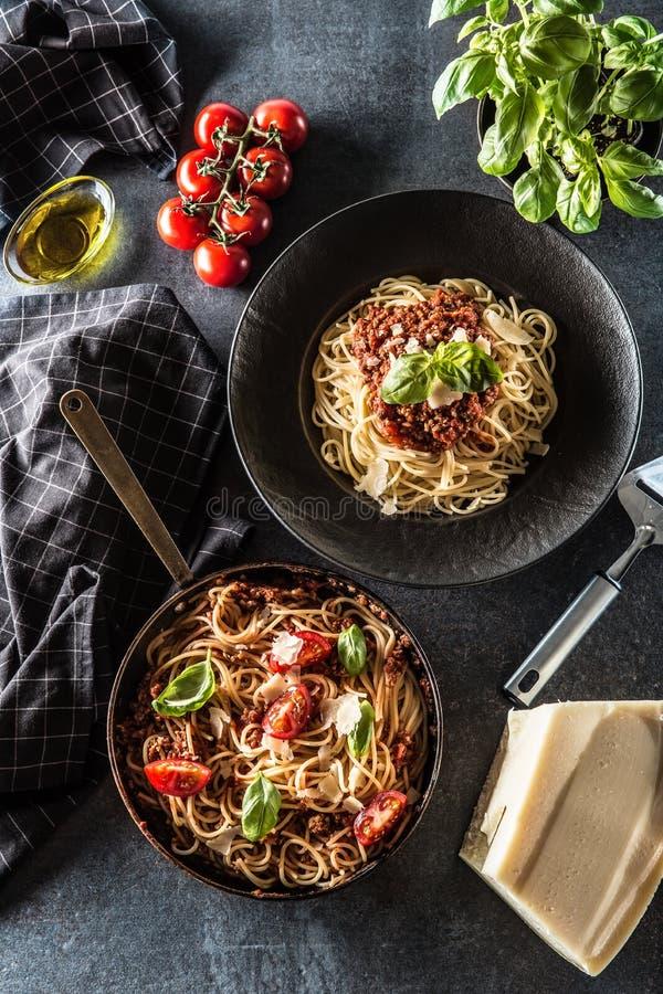 Dessus des spaghetti italiens Bolonais de pâtes de vue dans le plat et la casserole avec les tomates et le basilic image libre de droits