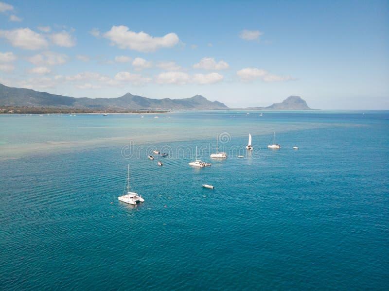 Dessus en bas de la vue aérienne des bateaux sur le récif de la plage tropicale de la rivière noire, île des Îles Maurice images stock