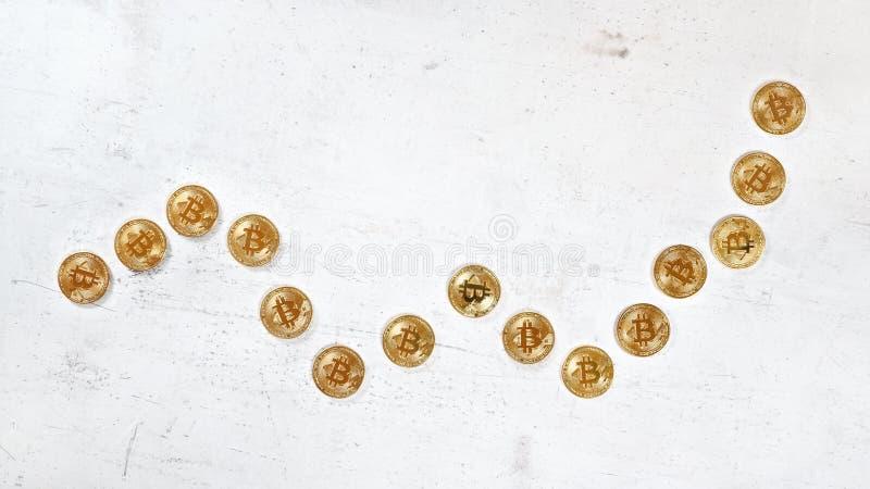 Dessus en bas de vue, bureau en pierre blanc de conseil avec les pièces de monnaie d'or de bitcoin dans la forme du graphique en  photo libre de droits