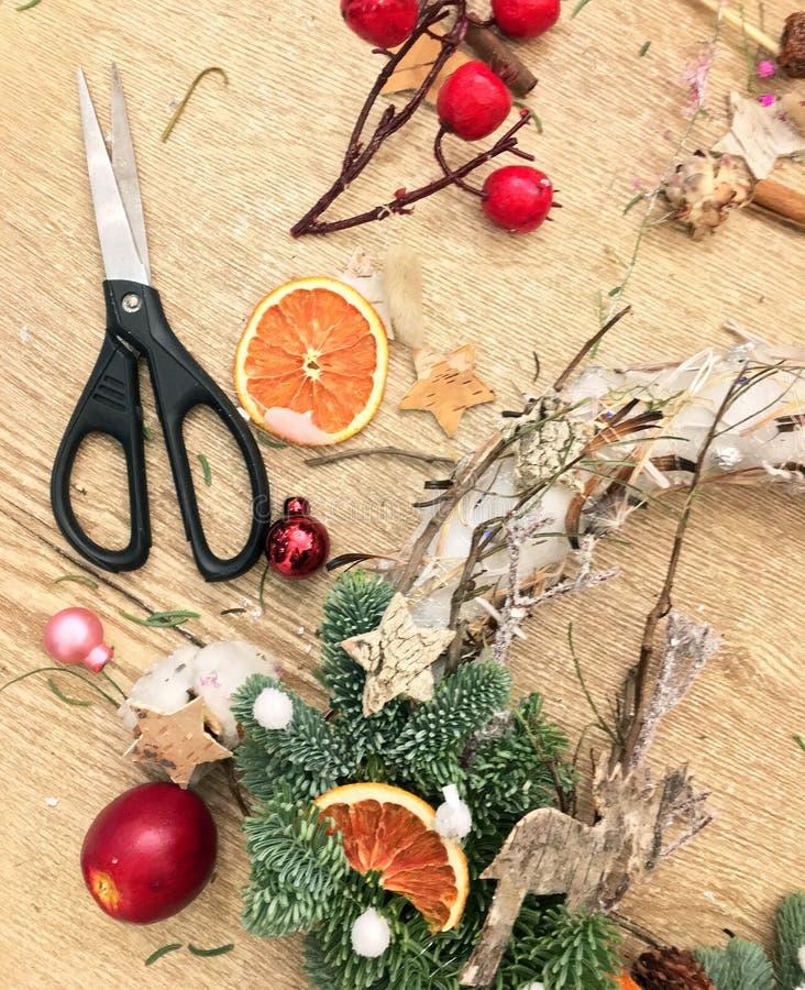 Dessus en bas de vue de la table de travail du fleuriste Fabrication de la guirlande de Noël image stock