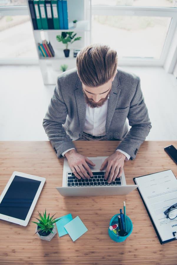 Dessus-vue de lieu de travail Le jeune homme d'affaires dactylographie sur son ordinateur portable image libre de droits