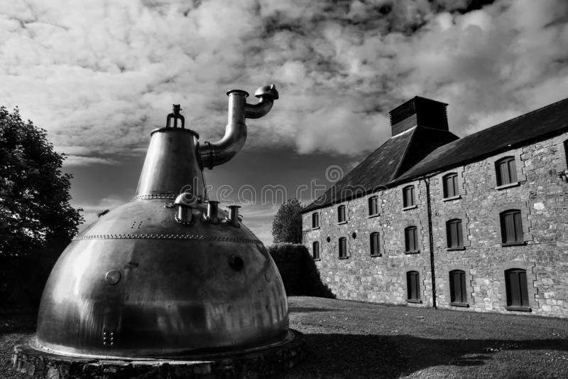 Destilería de cobre grande vieja del whisky en la fundación de piedra foto de archivo
