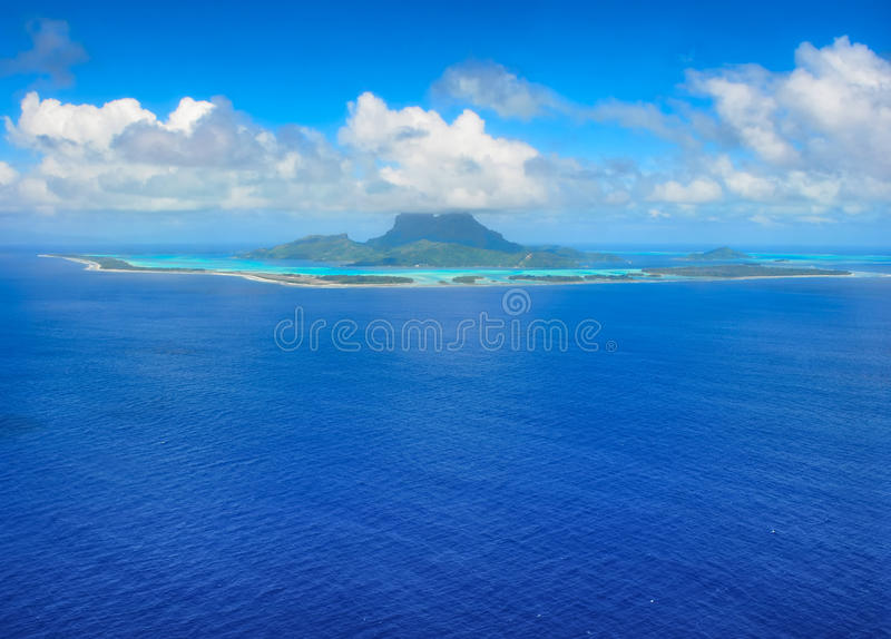 Destination Bora Bora. Aerial view from an airplane towards the honeymoon destination of the tropical island of Bora Bora with reef and turquoise lagoon. Bora royalty free stock photography