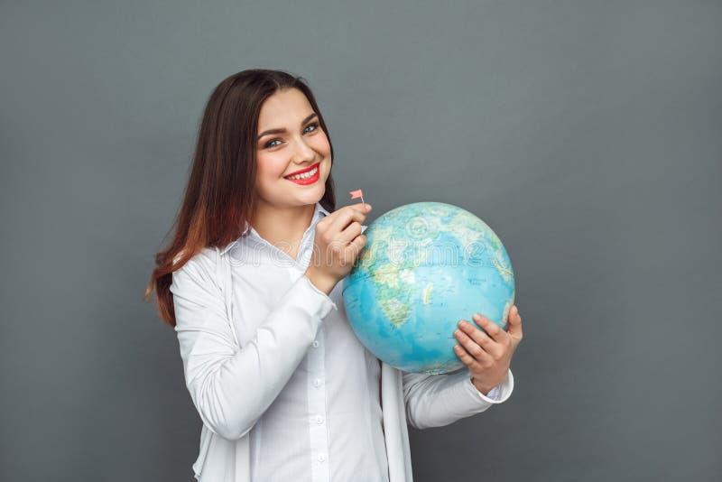 Destination neuve Position de femme d'isolement sur le drapeau de mise gris sur le sourire de globe gai photos stock