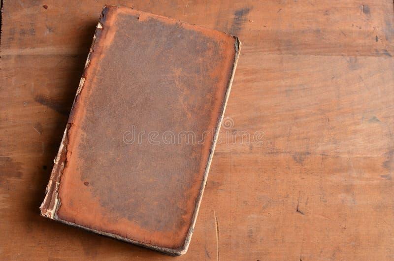 Destinerad bok för solbränt tappningläder som lägger på gammalt lantligt trä royaltyfri fotografi
