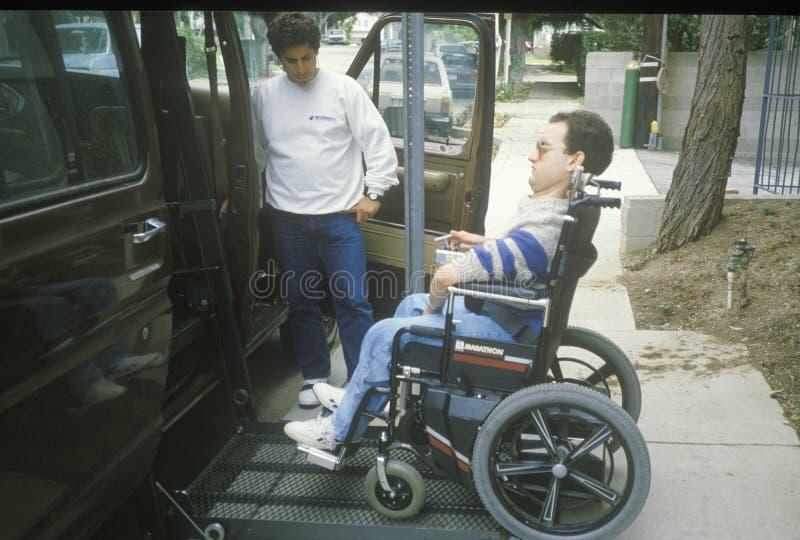 Destinerad ung man för rullstol som får in i den special utrustade skåpbilen fotografering för bildbyråer