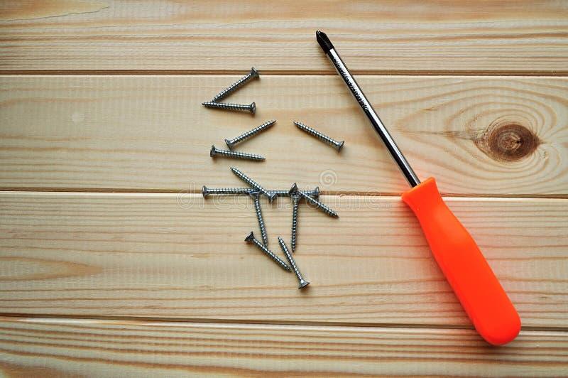Destornillador Phillips y algunos tornillos en la superficie de madera imagen de archivo libre de regalías