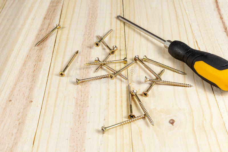 Destornillador y algunos tornillos de la cruceta que ponen en un piso de madera imagenes de archivo