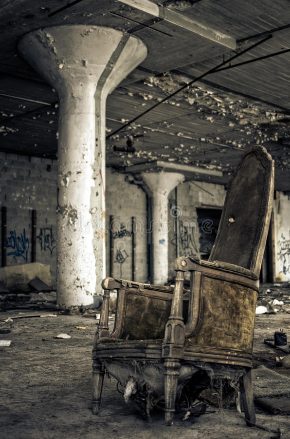 Destroyed Chair in Abandoned Factory. Old destroyed chair in an abandoned factory warehouse royalty free stock photos