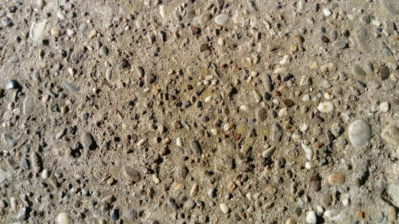 Destroyed concrete pavement. Small stones of different colors come out. A play of light and shadow on an uneven surface is created stock photography