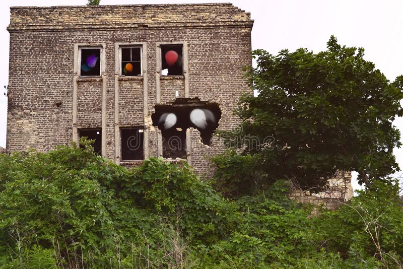 Destroyed house after bombing with lost souls in the windows royalty free stock photography