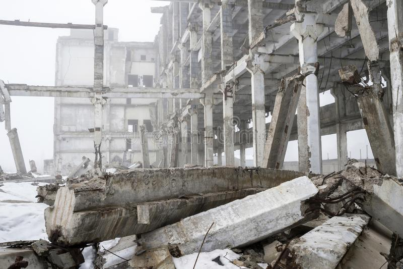 Destroyed large concrete building in a foggy haze with the remains of snow. Background royalty free stock photo