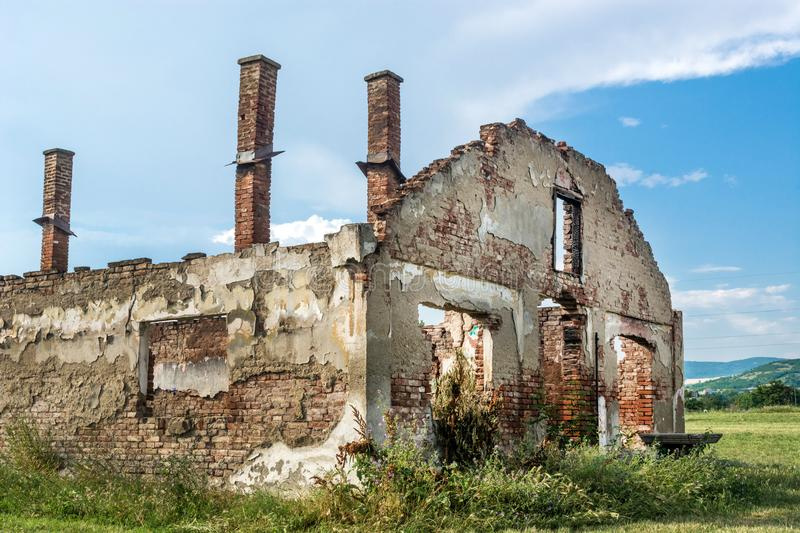 Destroyed old brick house without roof and with chimneys, broken windows, window frames, door and bricks. Abandoned destroyed old red brick house without roof royalty free stock photography