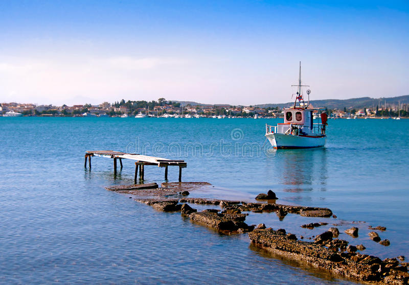 Destroyed pier and white small wooden fishing boat. View of Porto Heli town in the background. Greece stock image