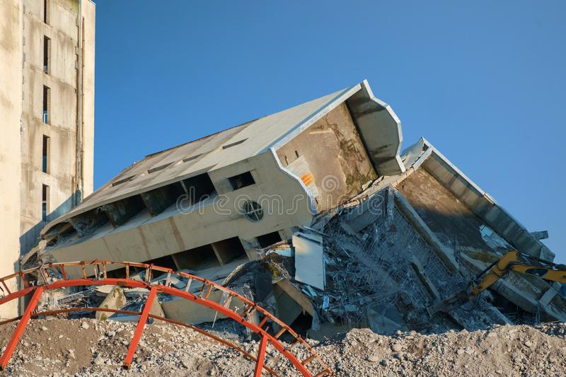 Destroyed and ruined big concrete building. With blue sky background stock images