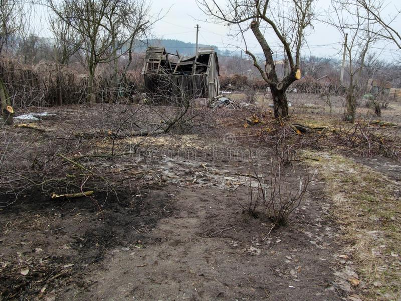 Destroyed wooden hut in the depths of the spring and autumn garden with leafless trees. Landscape of a private plot of land with stock photography
