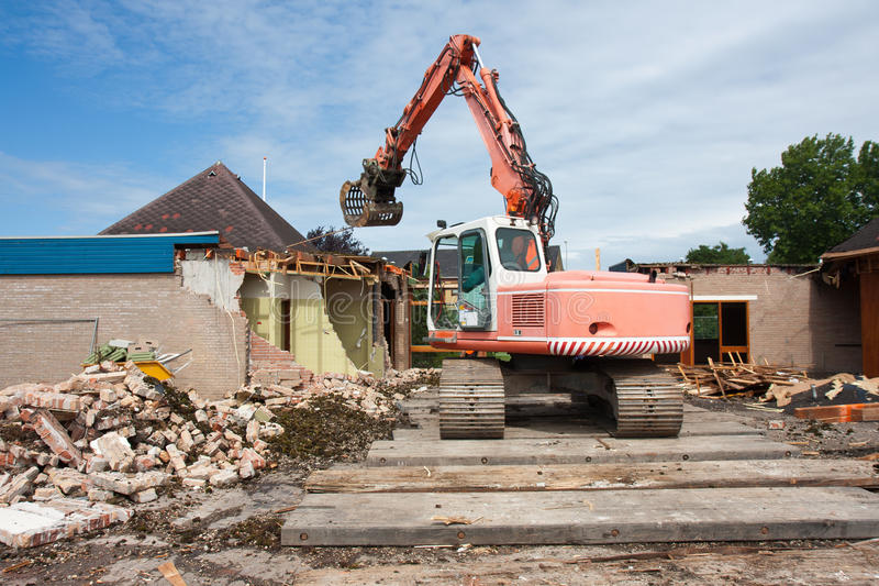 Destruction Of A Building By A Caterpillar Crane Stock Image