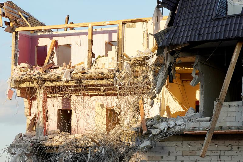 The destruction of a multi-storey building close-up. Floors and walls spread, reinforcement sticking out, wooden partitions. The. Roof of the building is broken stock images