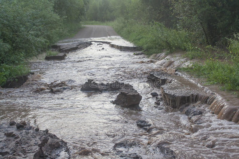 Destruction of the road. Water flows through a dirt road stock photography