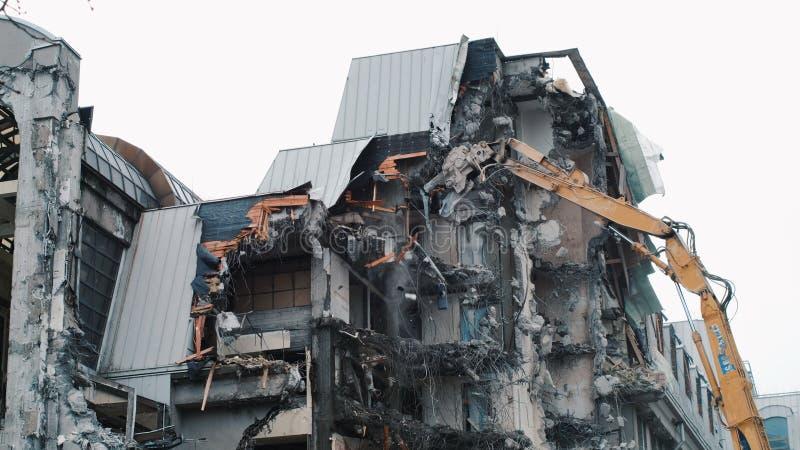 Destruição da casa com uma escavadora Desmontando a construção velha A máquina escavadora destrói as paredes do abandonado fotos de stock royalty free