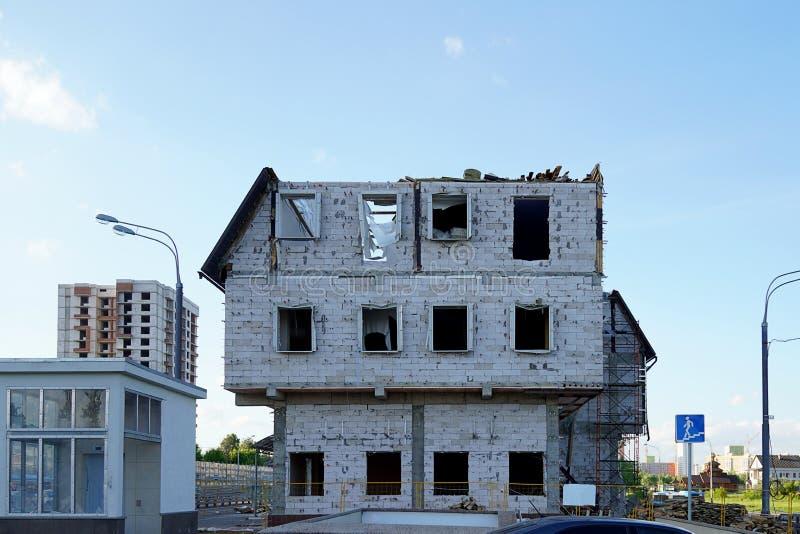 A destruição de uma construção do multi-andar A casa do bloco de espuma sem janelas e fachada Quebrado e desmontado o telhado fotografia de stock royalty free