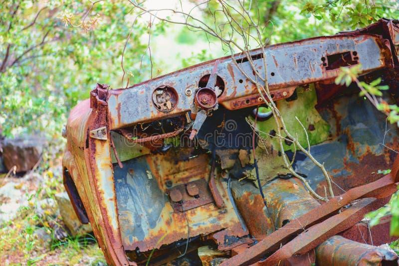 Destruição oxidada do carro abandonada em uma madeira imagem de stock