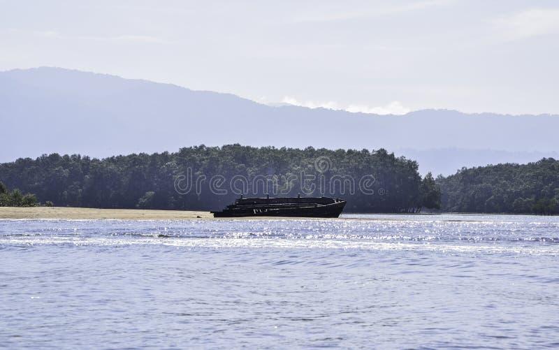 Destruições de madeira velhas do navio na praia pelo mar foto de stock royalty free