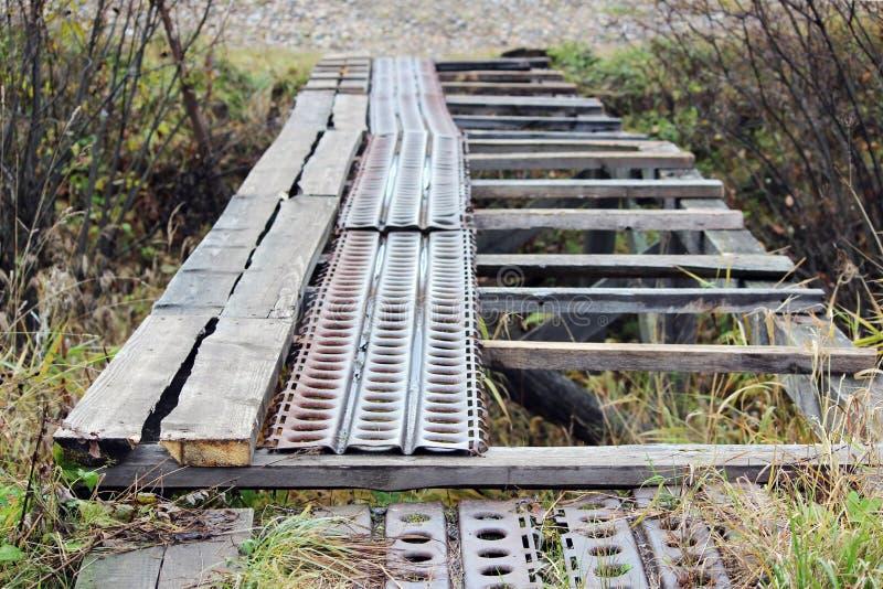 destruiu uma ponte através da vala das pranchas de madeira e dos perfis do metal imagem de stock royalty free