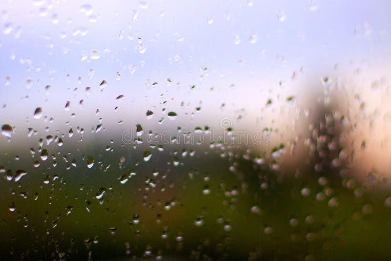 Deszcz krople na okno z zmierzchem behind zdjęcia royalty free