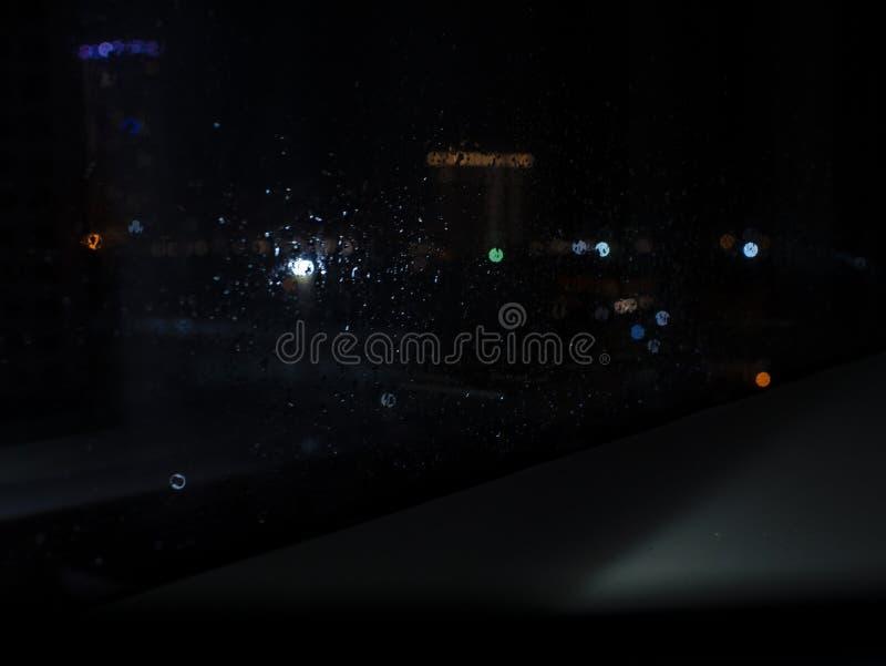 Deszcz opuszcza na okno z ulicznymi bokeh ?wiat?ami Na zewn?trz okno jest zamazany miasto obraz stock