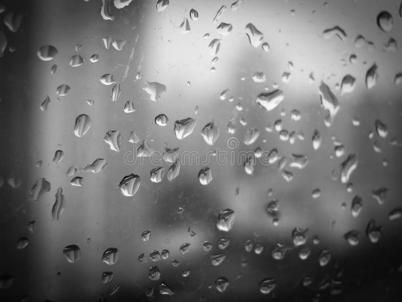 Deszcz opuszcza na szklanym okno miasto fotografia royalty free