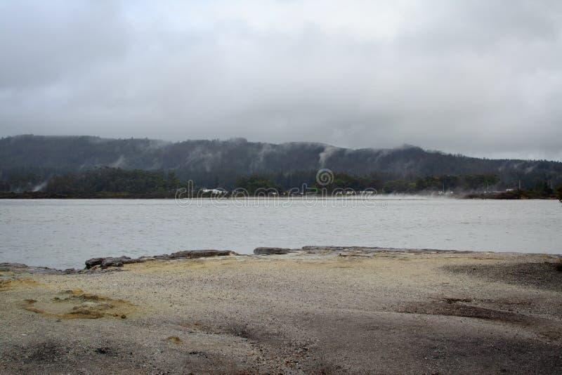 Deszczowy dzień przy jeziornym Rotorua Piaskowata plaża prowadzi siwieć wody i chmur niskie nadmierne odległe góry fotografia stock