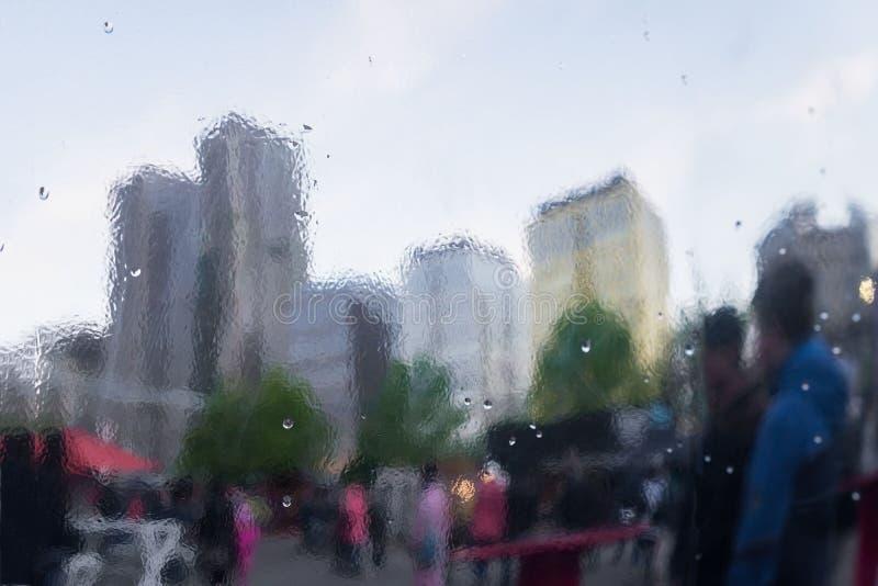 Deszczowy dzień w mieście Selekcyjna ostrość na raindrops Zniekształcający odbicie miasto i ludzie na metal powierzchni zdjęcie royalty free