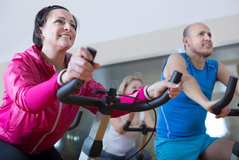 Det äldre folket gör sportar på motionscykeler arkivfoton