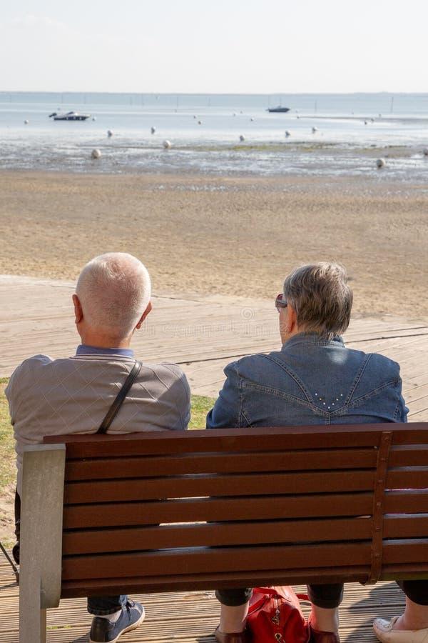 Det äldre paret ser strandhavet som sitter på bänk royaltyfri foto
