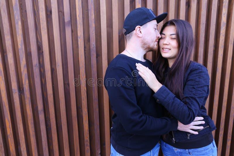 Det älskvärda paret som kramar och ser in i de ` s, synar, försiktigt royaltyfri bild
