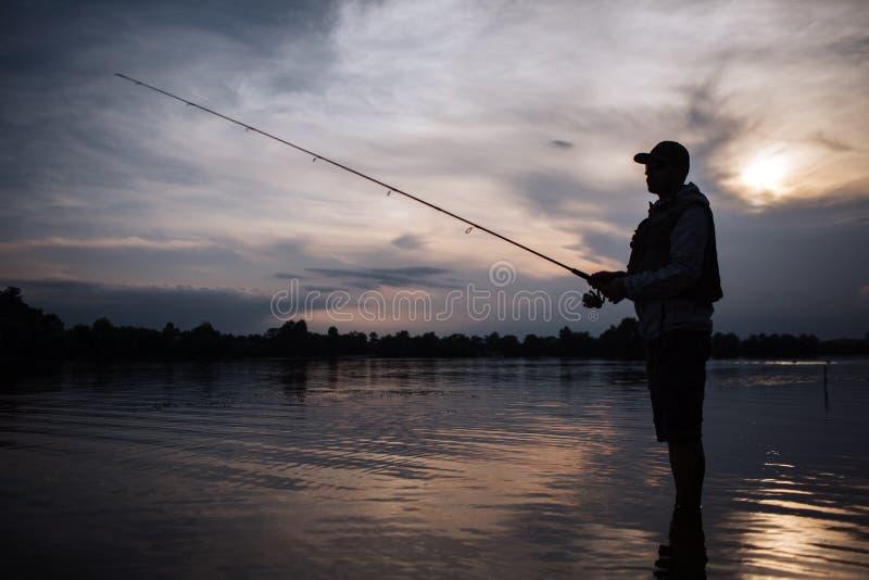 Det är aftonen utanför Fiskaren står i grunt och fiske Han rymmer den klipska stången i händer Det finns en rulle under den Honom royaltyfri fotografi