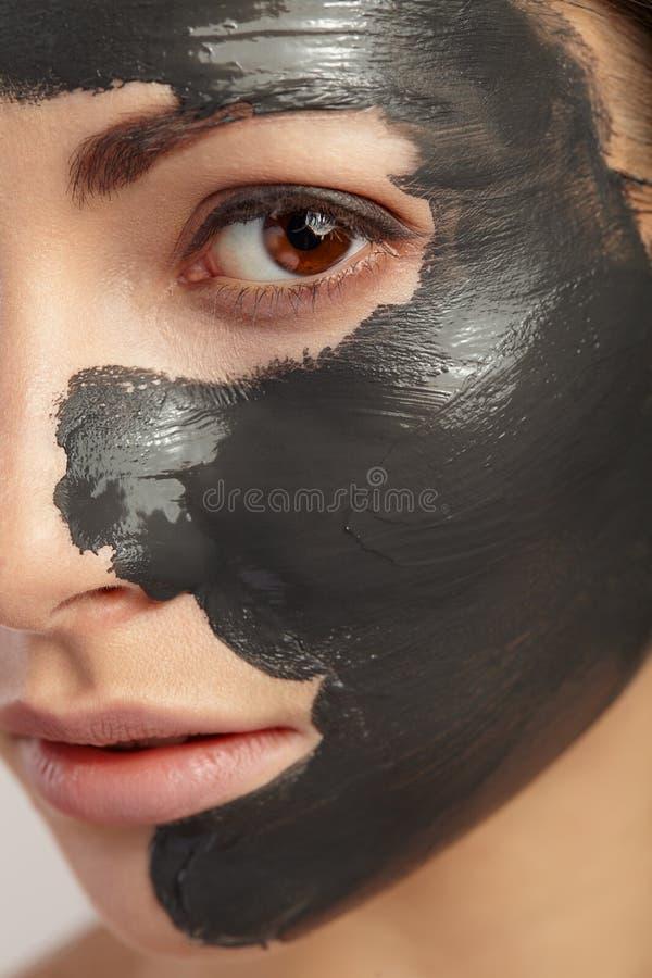 Det är den stora ståenden av flickan med den svarta leramaskeringen arkivfoton