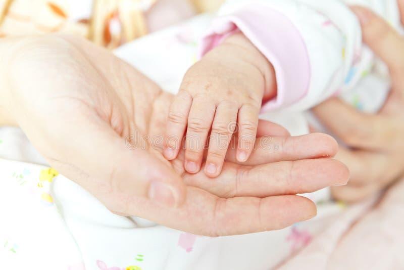 Närbilden av baby'sen räcker den hållande modern räcker arkivbilder