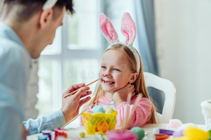 Det är så gyckel som förbereder sig för påsk med farsan Farsan och hans lilla dotter har tillsammans gyckel, medan förbereda sig  arkivbild