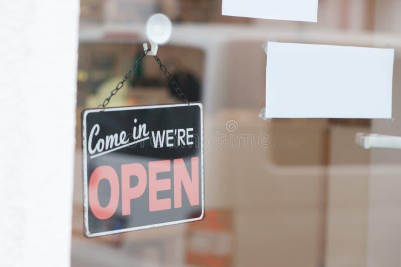 Det öppna tecknet på fönstret shoppar arkivbild