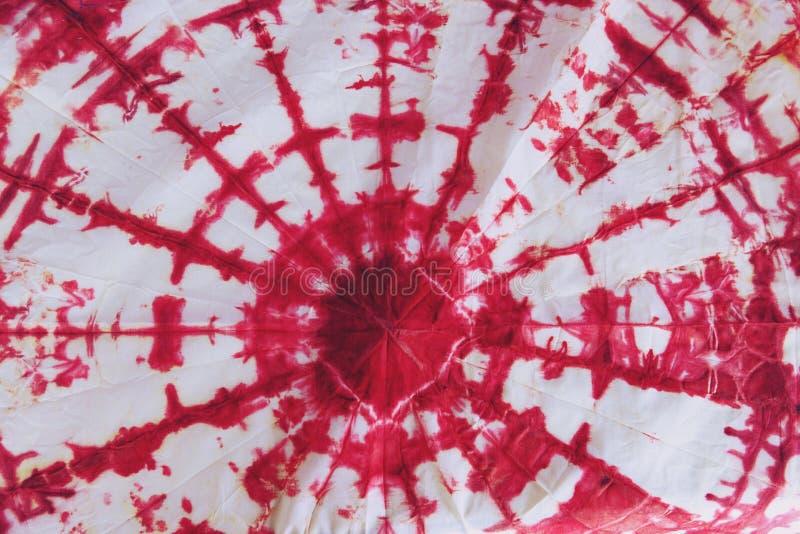 Det abstrakta bandet färgade tyg av röd färg på vit bomull arkivfoton