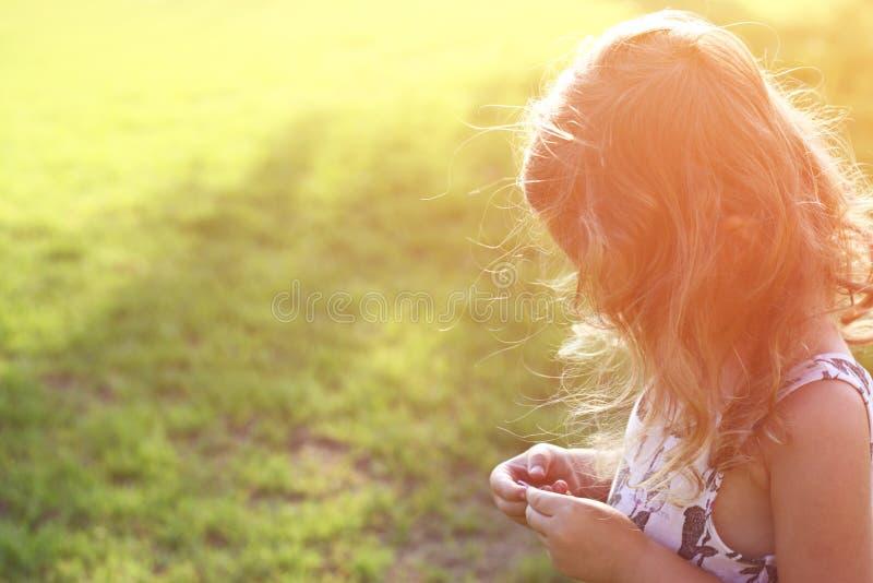 Det abstrakta fotoet av den tillbaka sidan av den lyckliga ungen som spelar på solnedgången i parkera, undersöker och äventyrar b arkivbild