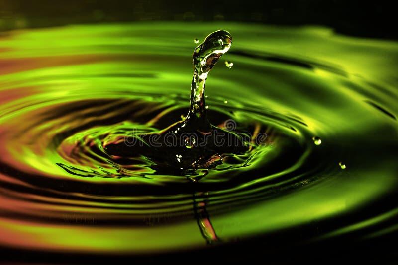 Det abstrakta fotoet av vatten tappar på trevlig röd bakgrund för gul gräsplan Trevligt textur- och designfoto arkivbild