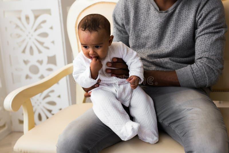 Det afrikansk amerikanfaderPlaying With Mixed loppet behandla som ett barn sonen hemma royaltyfri foto