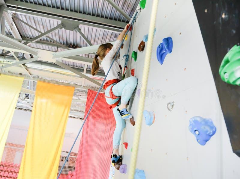 Det aktiva caucasian kvinnliga barnet är på klättraväggen arkivfoton