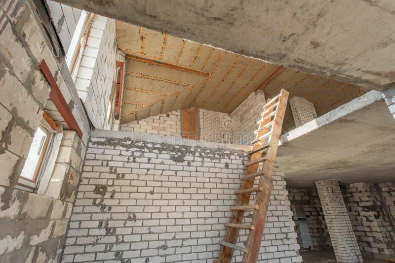 Det andra loftgolvet av huset genomgång och rekonstruktion Arbetande process av att värme inom delen av taket Hus arkivfoto