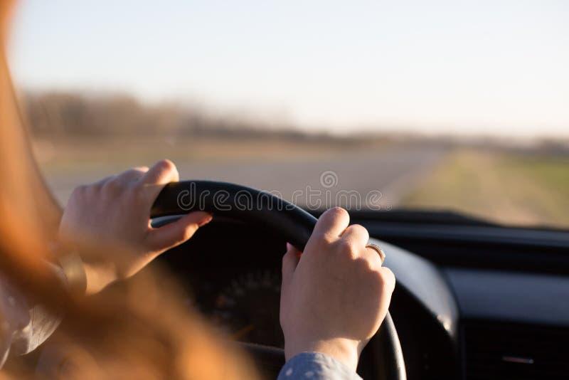 Det ansiktslösa skottet av den unga kvinnans händer på styrninghjulet, medan köra bilen, de kvinnliga stoppen hennes medel på sid royaltyfri fotografi