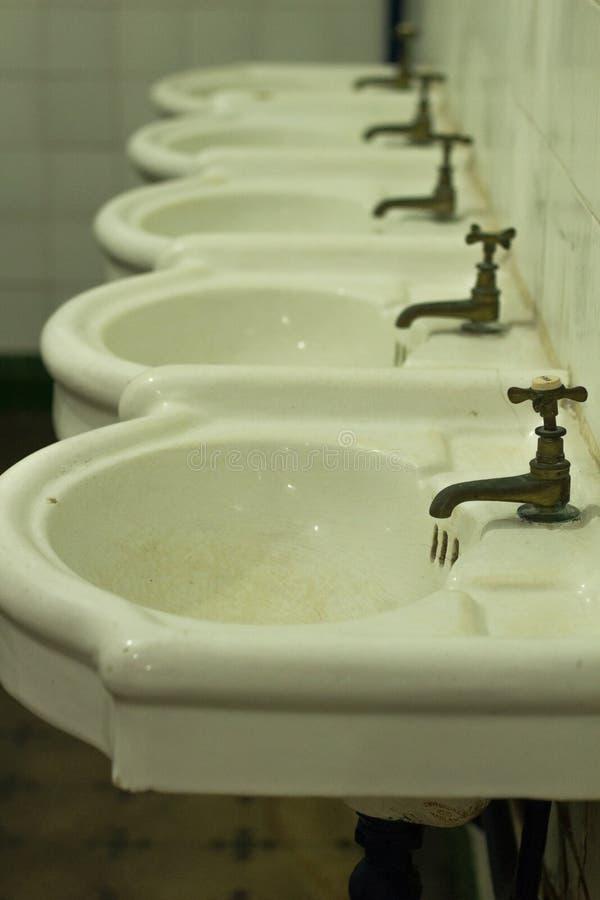 Det antika badrummet med vattenkranar sid - förbi - sidan fotografering för bildbyråer