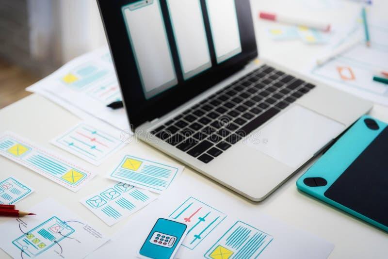 Det arbetande skrivbordet av den framkallande teknologimobiltelefonen för programmerare med skissar applikation på tabellen Använ royaltyfri bild